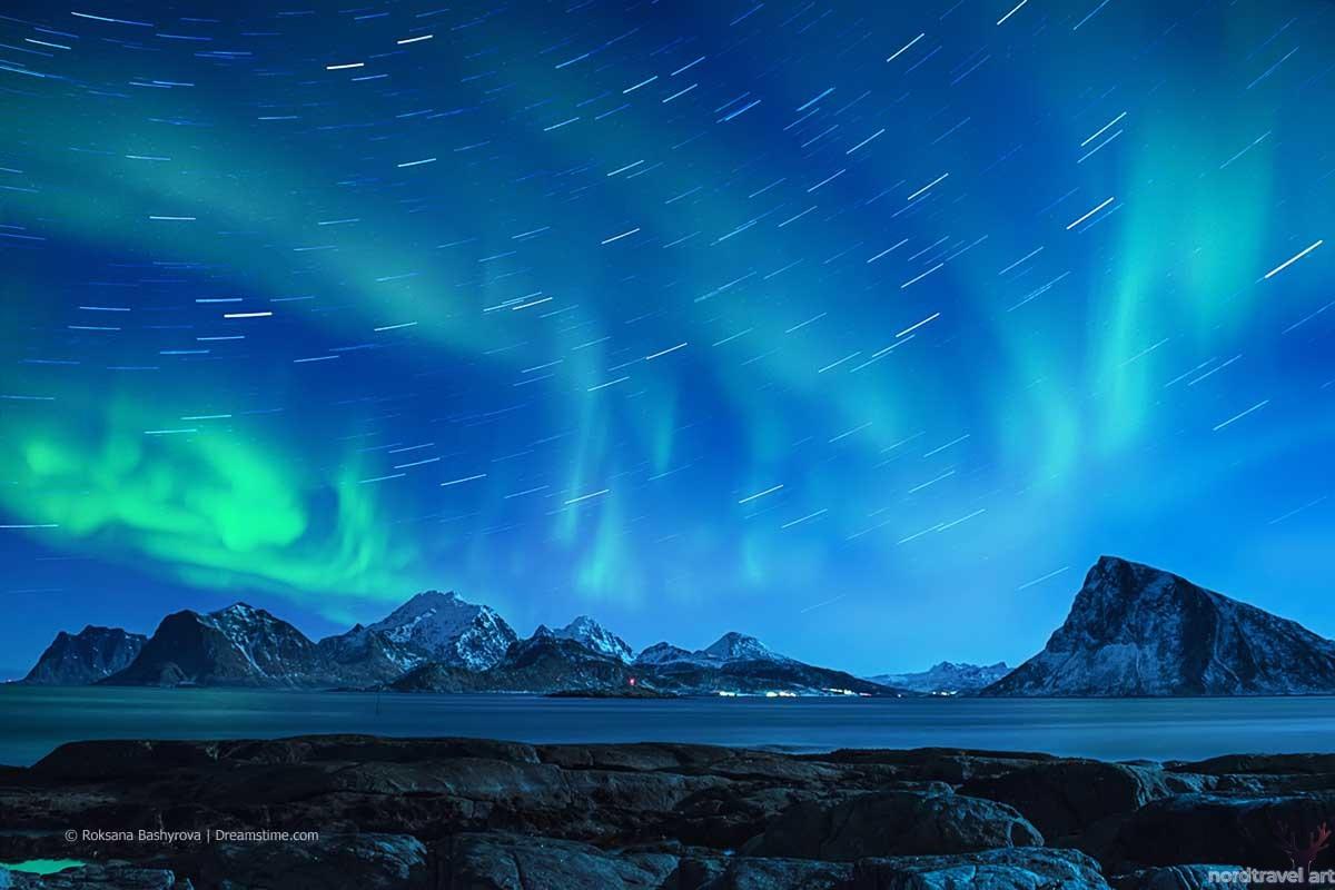 Природа и география Норвегии. движение звёзд и северное сияние в ночном небе над Лофотенскими островами